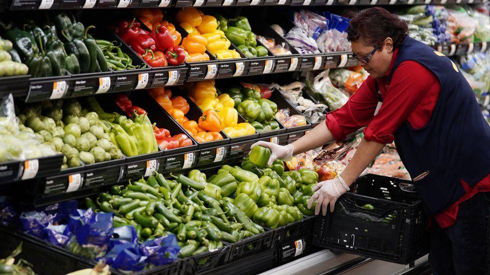 Walmart employee stacks vegetables