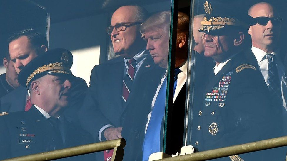 Mr Trump and Mr Giuliani attend an American football game in December 2016