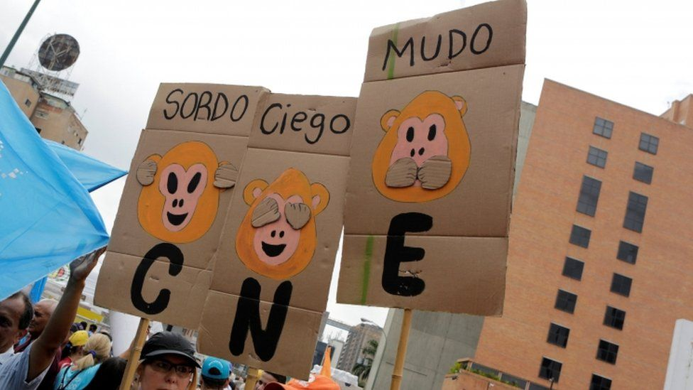 """Opposition supporters hold placards during a rally to demand a referendum to remove President Nicolas Maduro in Caracas, Venezuela, May 14, 2016. The placards (L-R) read """"Deaf"""", """"Blind"""" and """"Dumb"""". """"CNE"""" on the placards refers to the National Electoral Council. REUTERS"""
