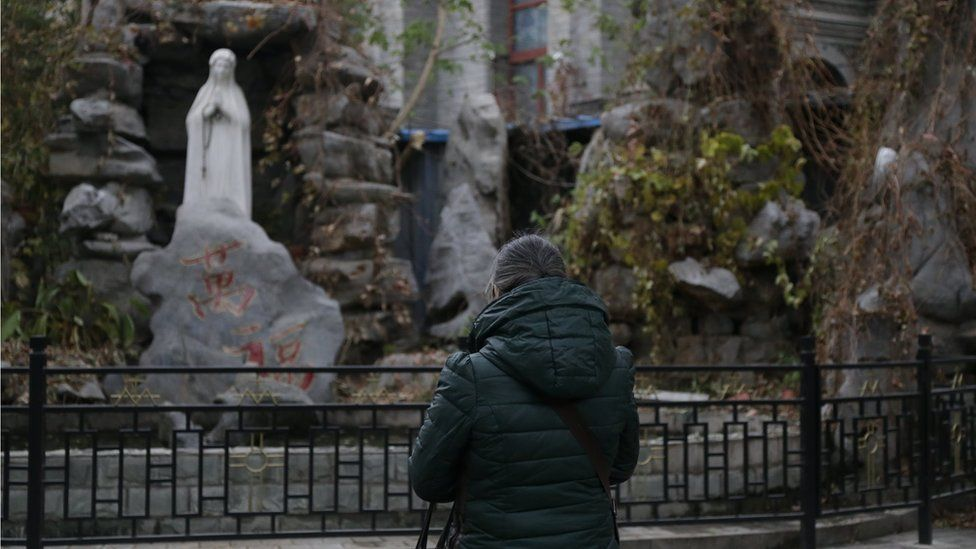 Woman, wrapped in a winter coat, prays in front of a statue of the Virgin Mary.