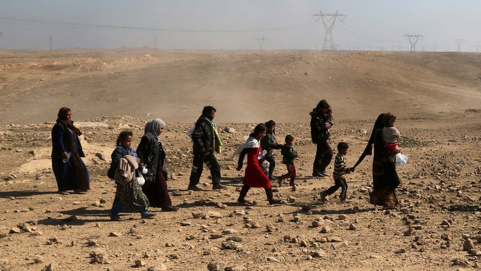 Displaced Iraqis flee their home near the western side of Mosul, 23 February