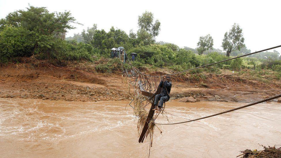 A man crosses a flooded Umvumvu river in Chimanimani, Zimbabwe - 18 March 2019