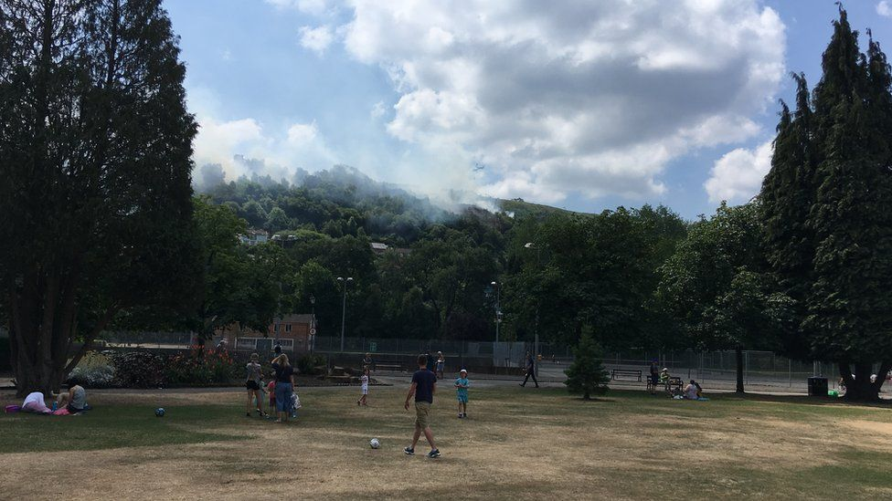 Cloud of smoke from a fire with people in a park looking at it from below. A helicopter is in the smoke cloud