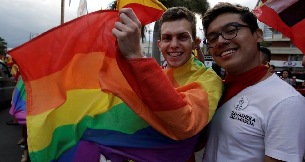 Supporters of Carlos Alvarado pose with a rainbow LGBT pride flag on 1 April, 2018.