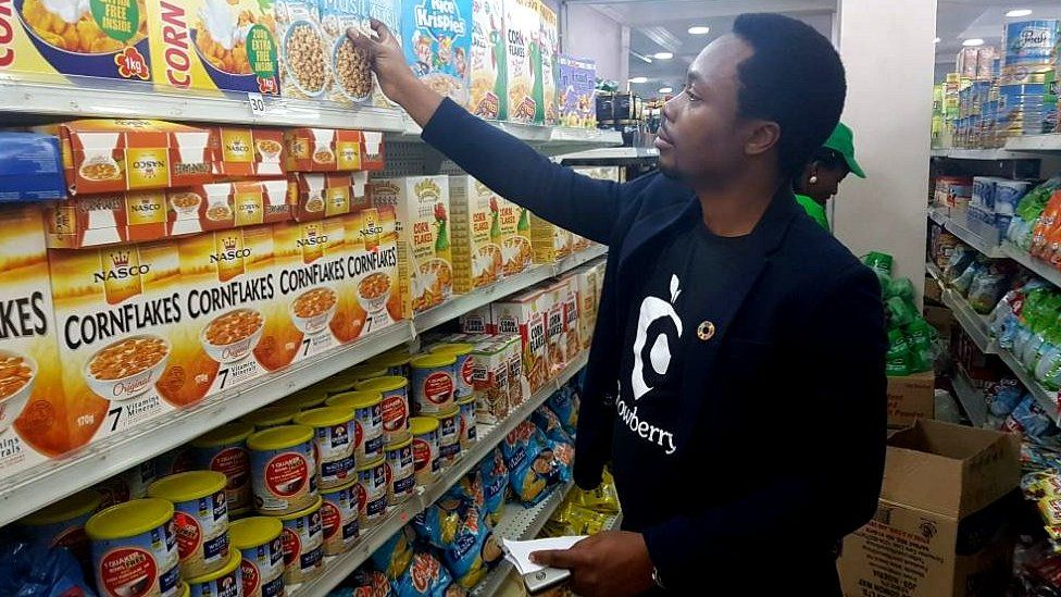 Oscar Ekponimo looking at boxes of cereal
