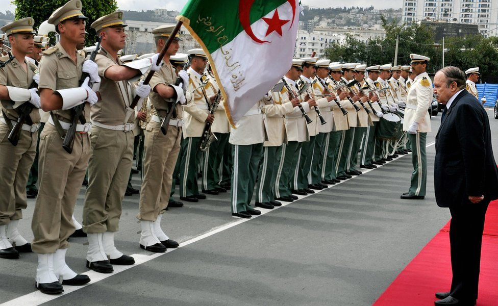 Algerian President Abdelaziz Bouteflika (R) salutes the national flag as he reviews a guard of honour in Algiers - 2009