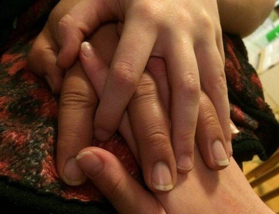 Three intertwined hands