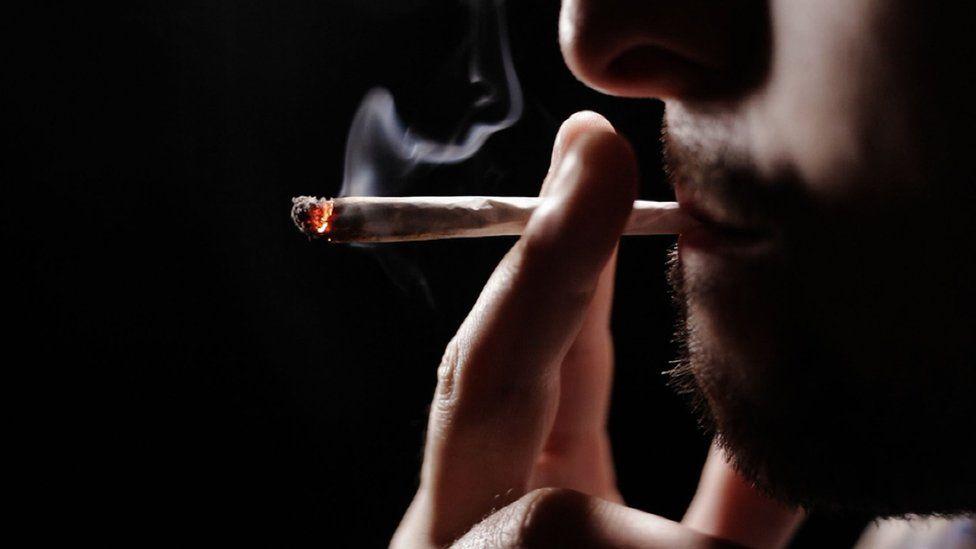 A man smoking a roll-up