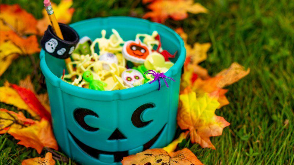 Teal pumpkin bucket with sweers in it