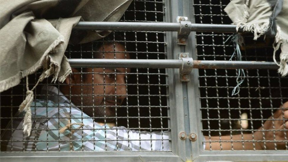 An Indian prisoner, convicted of involvement in the 2006 Mumbai train blasts, looks out from a police van on his way to a special court in Mumbai on September 16, 2015.