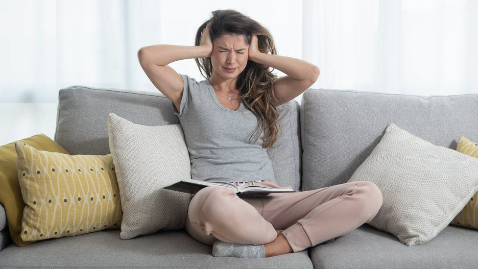 woman on sofa with hands over her ears