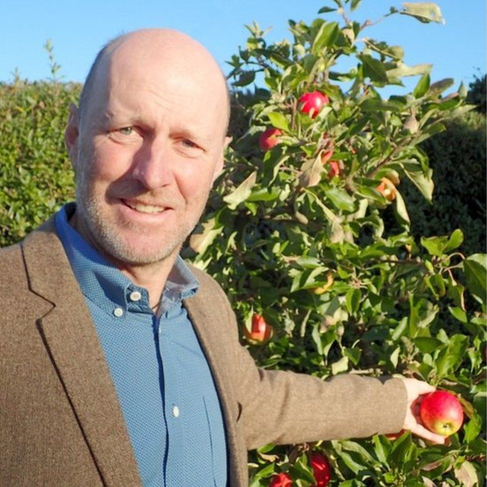 Crispin Hayes stands beside apple tree