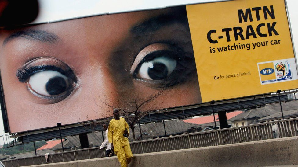Man standing in front of an MTN billboard