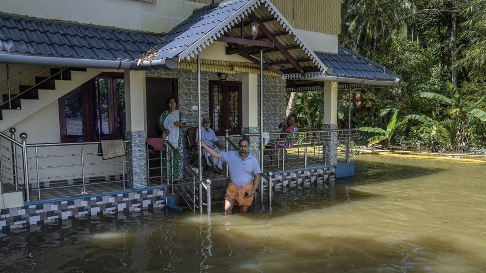 A family outside their flooded house