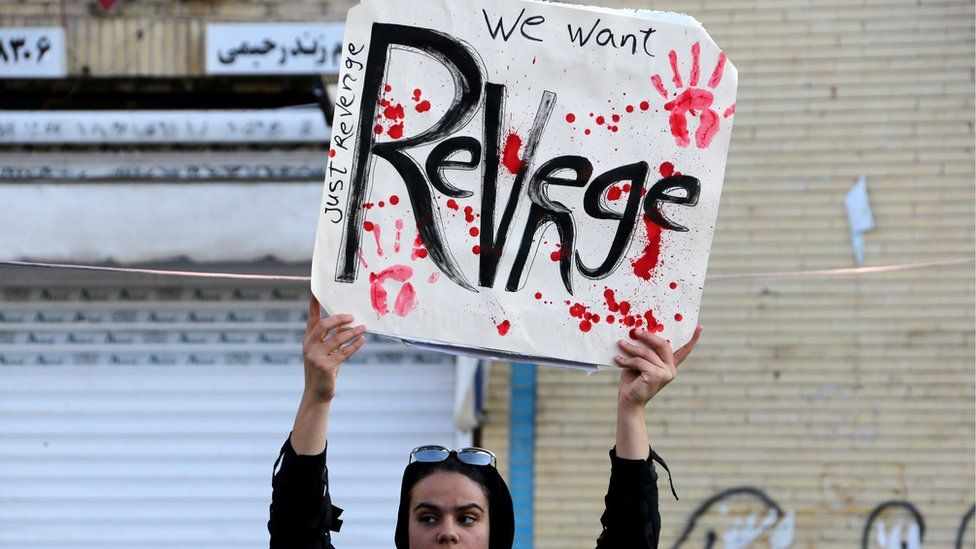 An Iranian mourner holds a placard in funeral procession saying 'We want revenge'