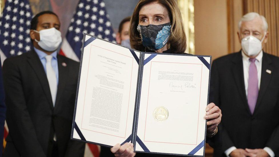 Speaker of the House Nancy Pelosi holds the signed Article of Impeachment against US President Donald J. Trump during an engrossment ceremony in the Rayburn Room at the US Capitol in Washington, DC, USA, 13 January 2021.