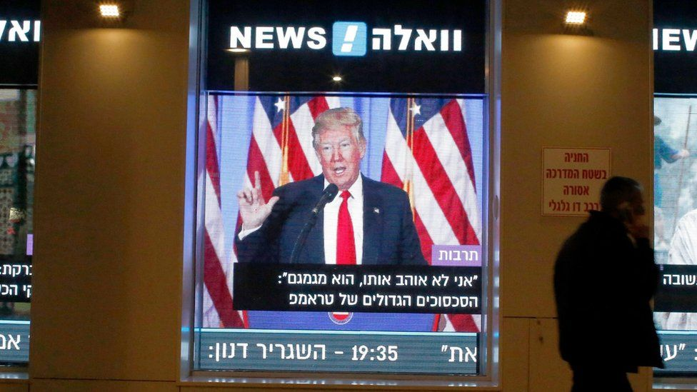A man walks past a screen in Tel Aviv, Israel, showing the inauguration of Donald Trump on 20 January 2017