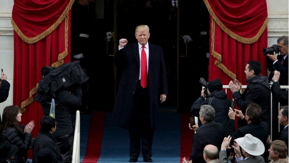 Donald Trump raising a fist, surrounded by cameras, arriving to his inauguration ceremony