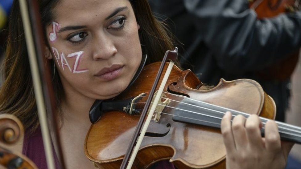 "A musician of the conservatory of the National University of Colombia plays the violin with her face painted that reads ""peace"" during protests and a national strike against the government of President Ivan Duque on November 27, 2019 in Bogota, Colombia"