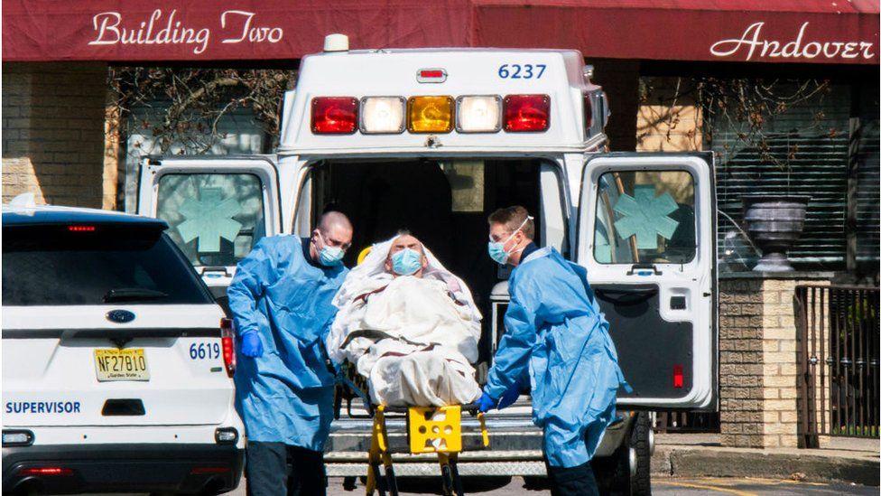 Paramedics load a patient into an ambulance