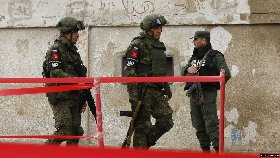 Members of the Russian military police walk past a Syrian regime soldier in Homs, Syria