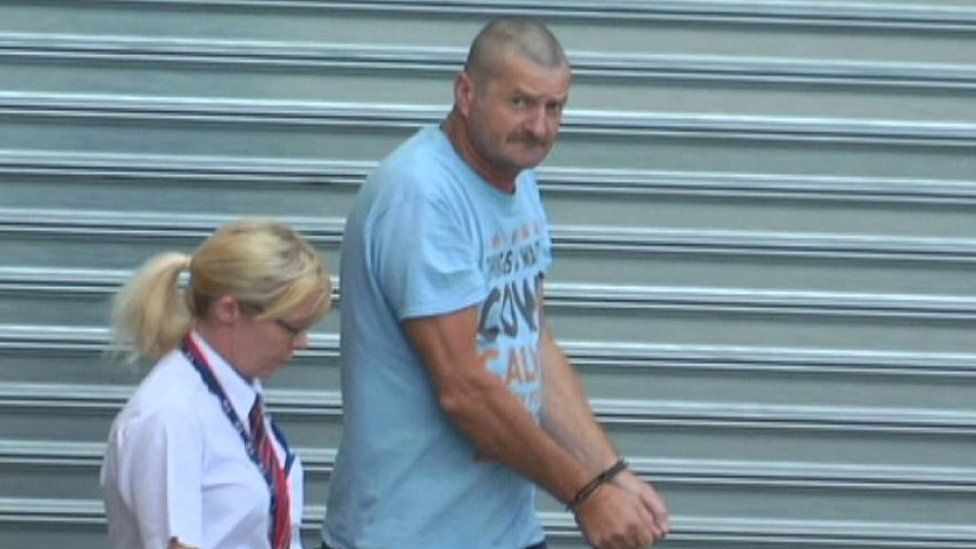 Gene Charles Bristow in handcuffs is escorted by a guard to Adelaide's District Court