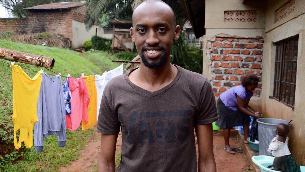 Yoza Co-founder, Nicholas Kamanzi with cleaner Naiga in the background