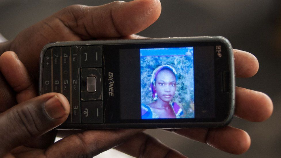 The mother of Rifkatu Galang, one of the abducted Chibok girls, holds a phone showing her photo - April 2016