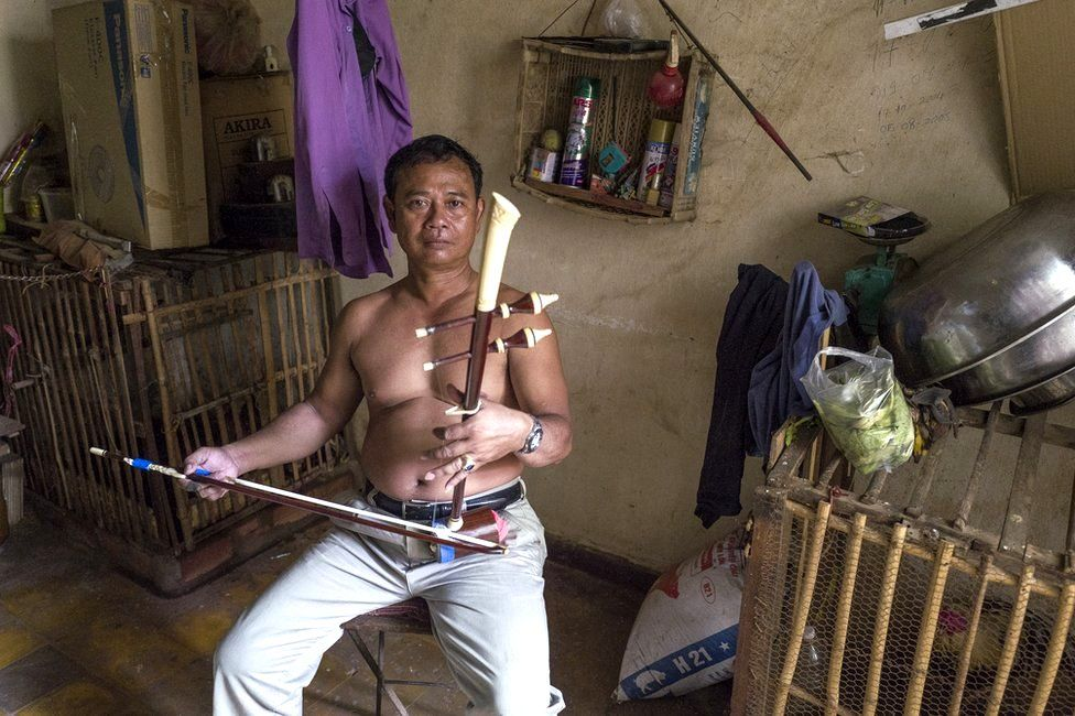 Resident playing on a traditional instrument