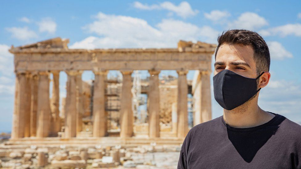 A man wearing a face mask, posing in front of the Parthenon in Athens, Greece