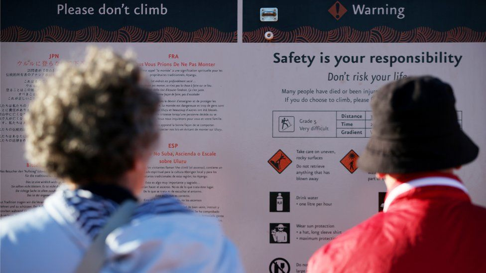 Visitors read the 'please don't climb' and warning signs at the base of Uluru