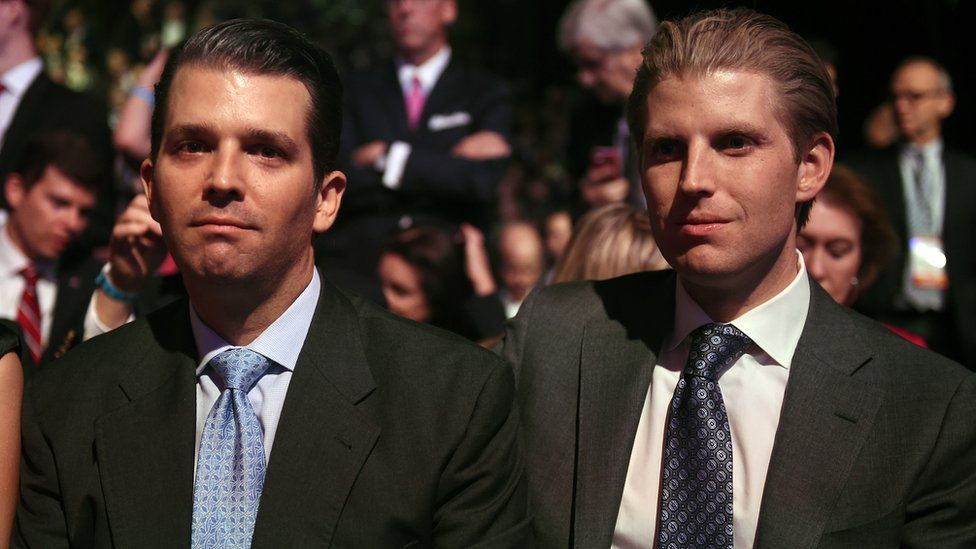 Donald Trump's sons Eric Trump (L) and Donald Trump Jr. wait for the start of the CNBC Republican Presidential Debate, October 28, 2015