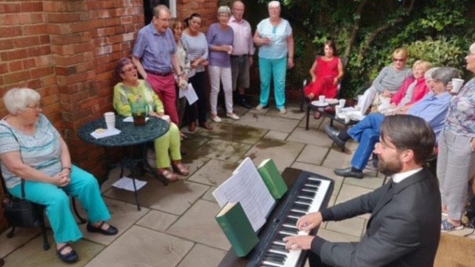 Father Lee Taylor playing the piano to a crowd as his annual garden party, before Covid restrictions came in