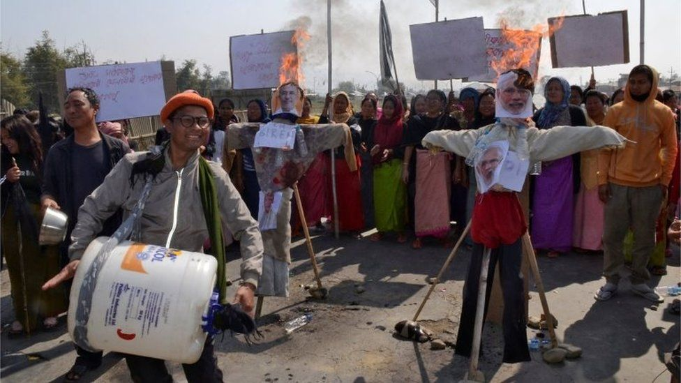 """A man beats an improvised drum next to burning effigies depicting India""""s Prime Minister Narendra Modi and Chief Minister of the northeastern state of Manipur Nongthombam Biren Singh, during a protest against the Citizenship Amendment Bill, in Imphal, India, February 12, 2019"""