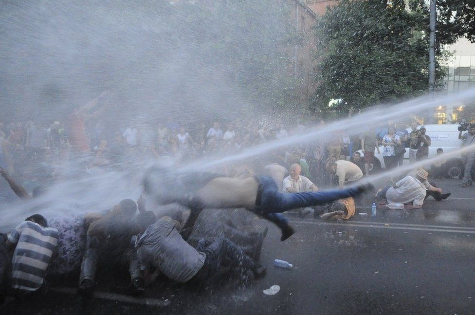 Protesters are hit by a jet of water in Yerevan, Armenia