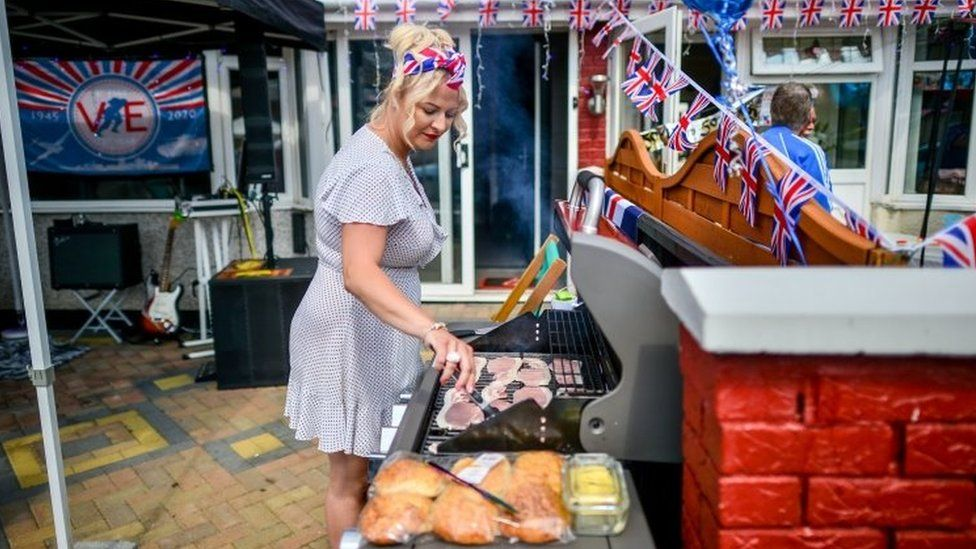 Laura Stacey turns bacon on the BBQ outside her home on Novers Park Road, Knowle, Bristol, on VE Day earlier in May 2020