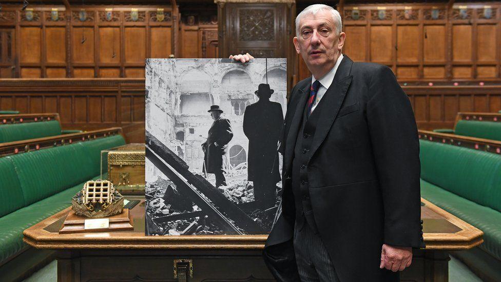 Sir Lindsay Hoyle holds a photo of Churchill surveying the wreckage