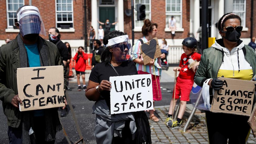 Demonstrators hold placards