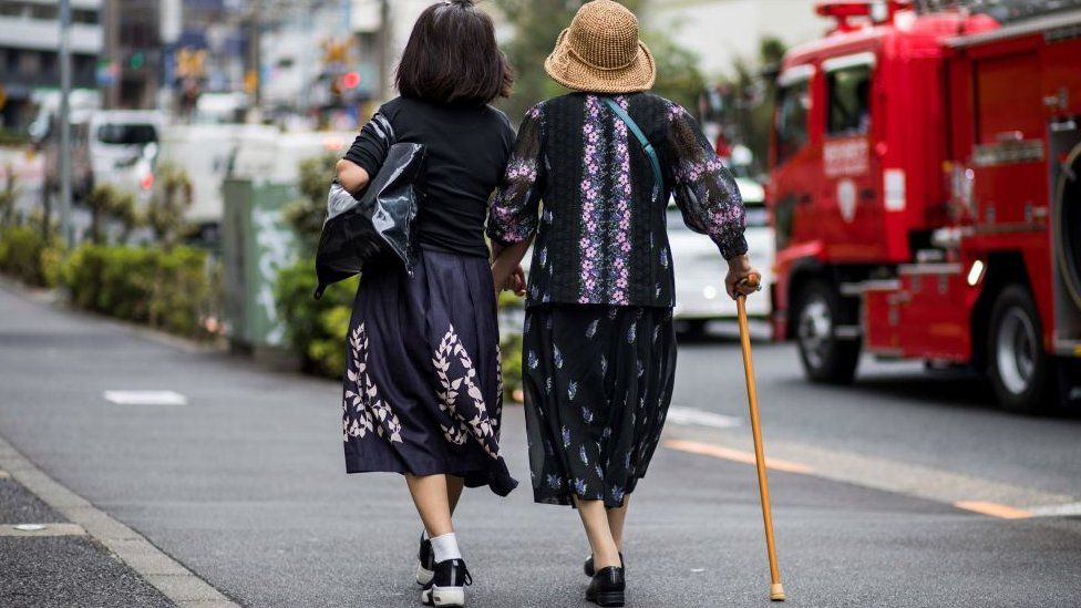 An elderly woman is escorted along a busy road in Tokyo on October 3, 2019.