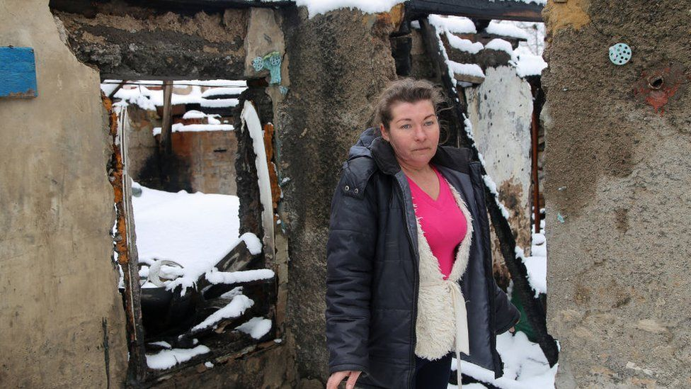 A woman outside her shell-damaged house near Donetsk, Ukraine, in March 2021