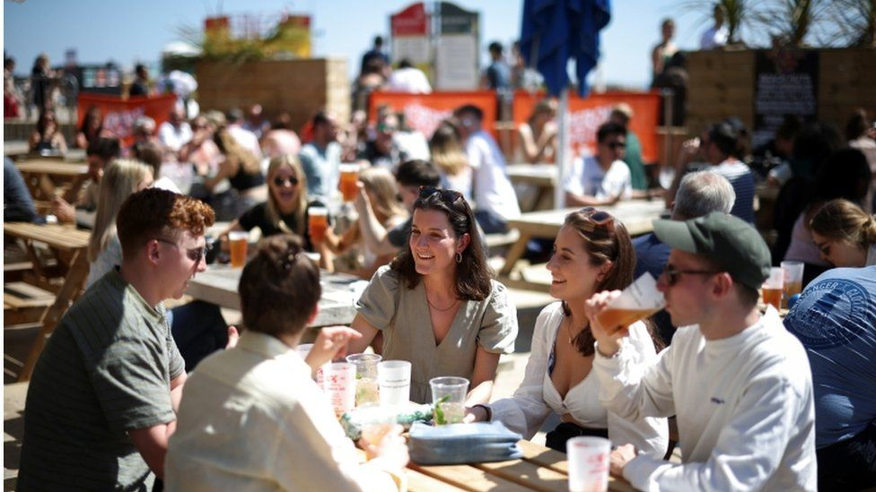 People sit at an outdoor bar as they enjoy the hot weather on Brighton pier, in Brighton