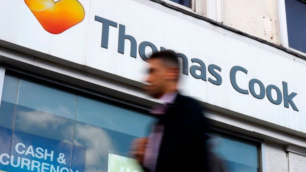 A pedestrian walks past a closed branch of a Thomas Cook travel agent's shop in London