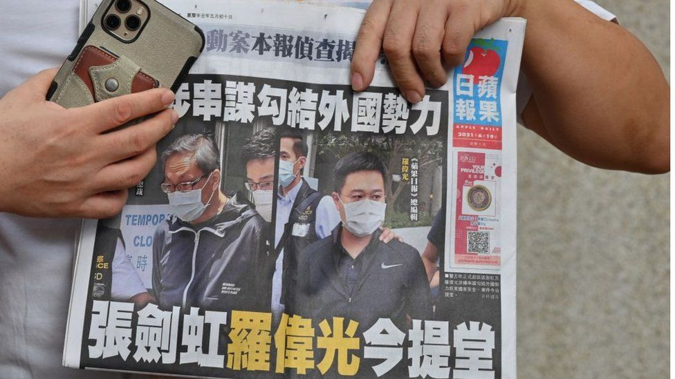 A supporter of two executives from Hong Kong's pro-democracy Apple Daily newspaper, chief editor Ryan Law and CEO Cheung Kim-hung, holds up a copy of the newspaper during a protest outside court in Hong Kong on June 19, 2021.
