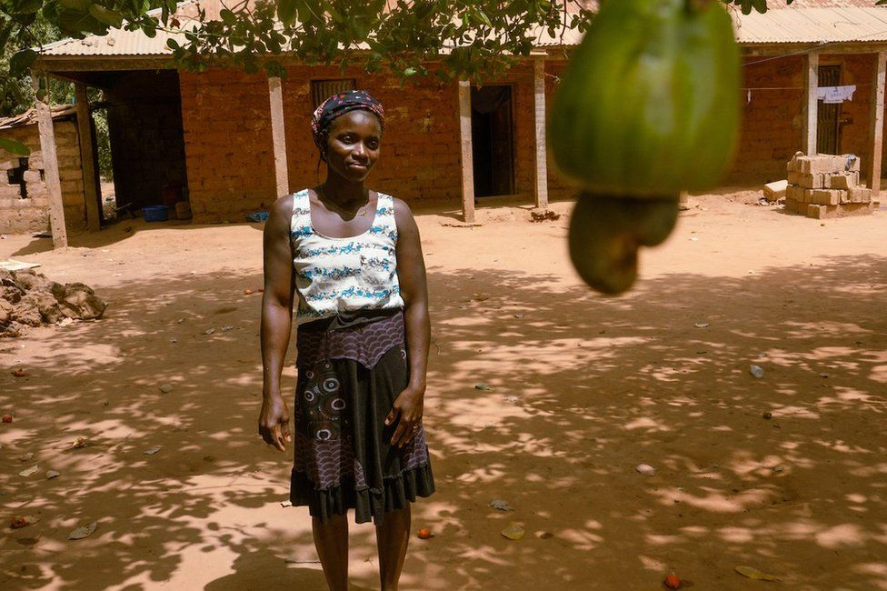 Meia Nianta poses for a portrait outside of her home that sits next to her her 1.5 hectare cashew farm just outside of the capital city, Bissau. She said the harvest starts in March and wraps up around June in the West African country. She usually works from mid-afternoon until late in the evening.