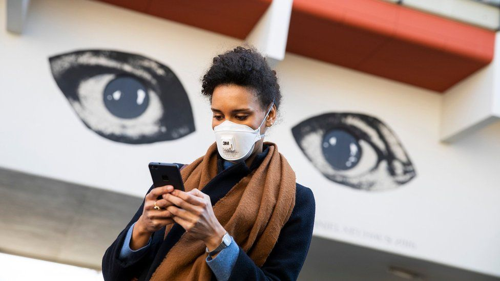 Woman using smartphone by graffiti of two eyes