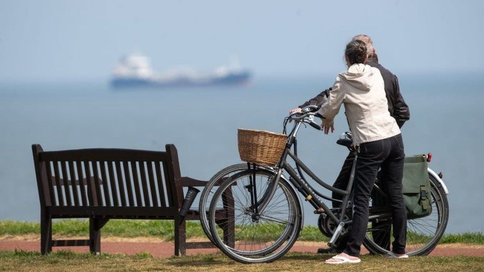 People take a break in their daily exercise at Gorleston-on-Sea in Norfolk as the UK continues in lockdown