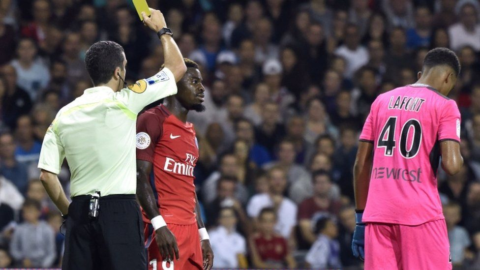 Paris Saint-Germain's Ivorian defender Serge Aurier (2nd L) receives a yellow card by French referee Franck Schneider during the French L1 football match between Toulouse (TFC) and Paris Saint-Germain (PSG) on 23 September 2016
