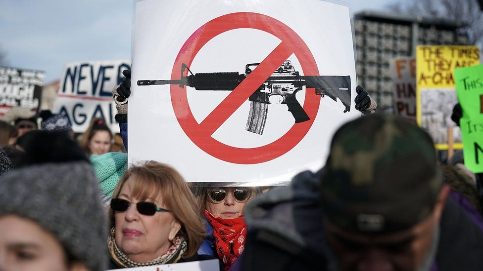 People hold signs as they wait for the beginning of the March for Our Lives rally on 24 March, 2018