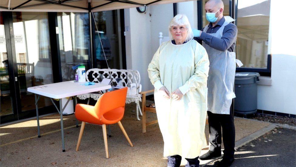 Fiona Scott puts PPE on