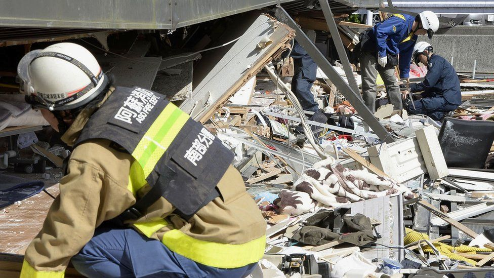 Police and fire fighters try to rescue residents trapped inside an apartment in Minamiaso, Kumamoto prefecture, southern Japan (16 April 2016)
